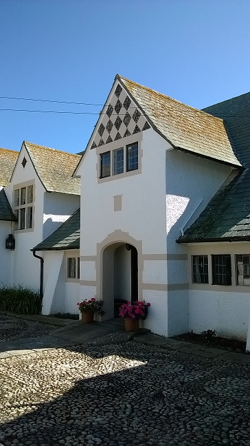 A clear blue sky and neatly pebbled road lead to Bill House, a white home in Selsey, featuring diamond tile design above the first floor windows