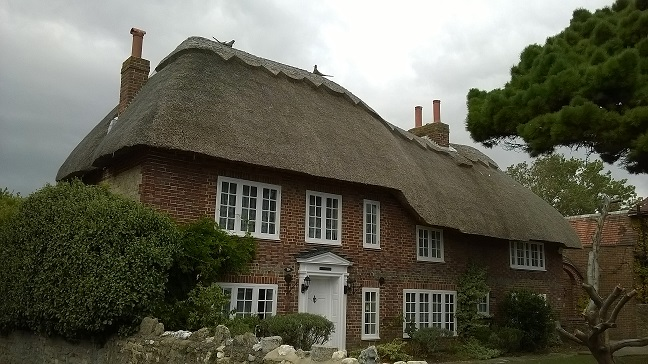 Homestead House is a red brick thatch cottage with white framed windows and front door. The front garden is exceptionally well maintained.