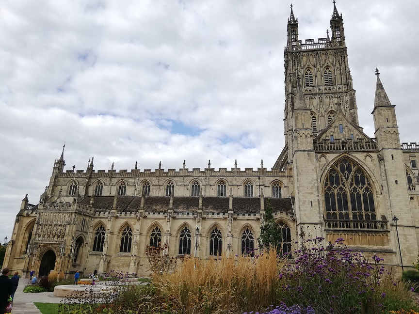 Exterior photograph of Gloucester Cathedral, showing the main entrance, bell tower and gardens