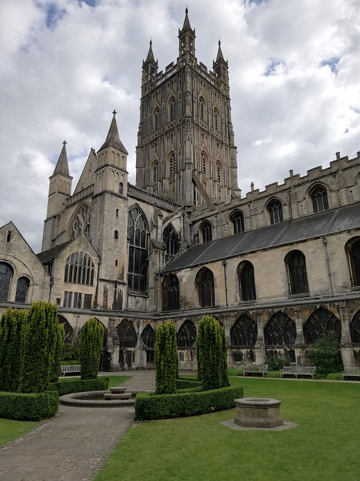 View of the bell tower from the cloisters garden, Gloucester Cathedral, with little shrubs and wells in the garden, and large windows of the cathedral visible