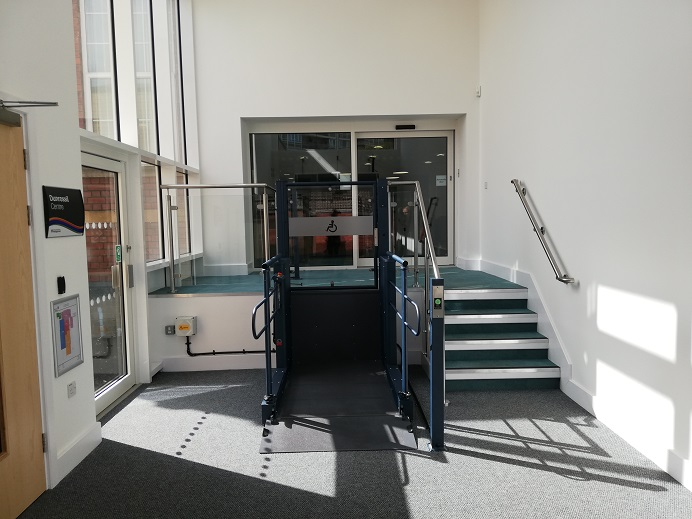 Stairs and a wheelchair lift bring you up to automatic door. The carpets are light grey and teal green. A side door leads to a community centre, and another side door leads to the garden