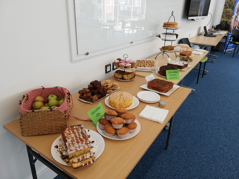 Apples and cakes line two tables. Including brownies, lemon drizzle, victoria sponge, cupcakes, marmalade cake, coffee and walnut, chocolate cake, chocolate and vanilla and fruit cake.