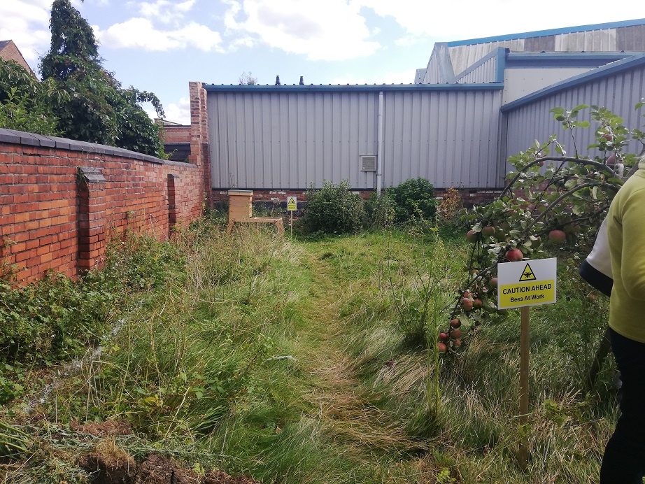 A yellow sign stating bees at work warns of the beehive at the very back of the garden, away from the members of the public