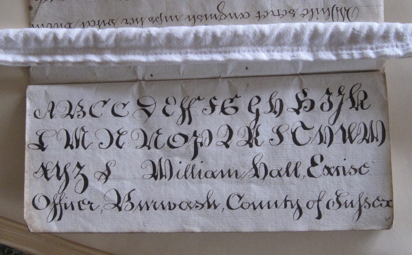 Page of a book with handwritten alphabet in.