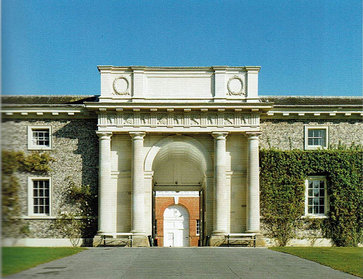 Colour photograph of the front entrance to the stables, with a neo-classical design of columns and an archway. Fauna grows up the walls either side of the main arch entrance.