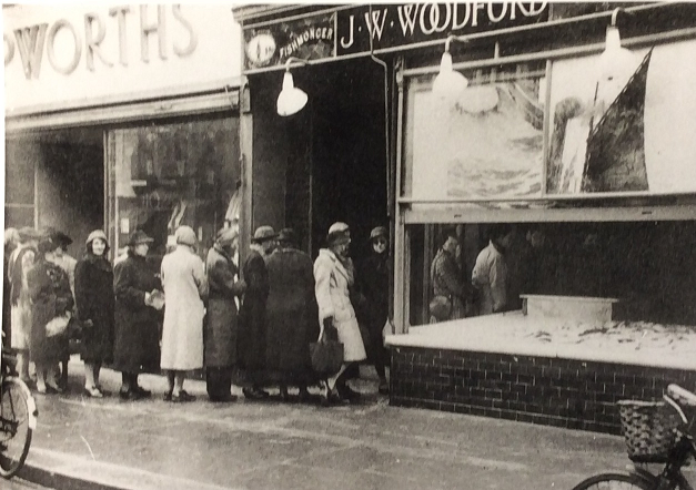 A black and white image showing a line of woman queuing to collect rationed fish supplies