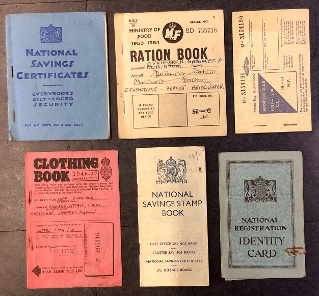 Six booklets held by a member of the public during the rationing period, including a blue National Savings Certificates booklet, a Ration book, a Petrol Ration book, a red Clothing Ration book, a slim National Savings Stamp Book, and a blue National Registration Identity Card