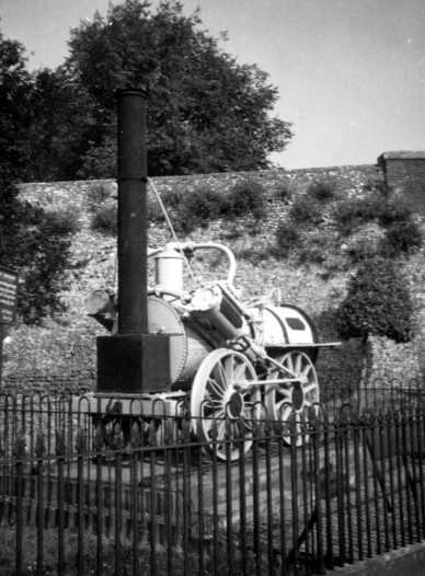 An early locomotive on display behind railings.
