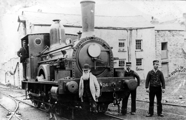 Three railway employees stand in front of a huge steam engine.