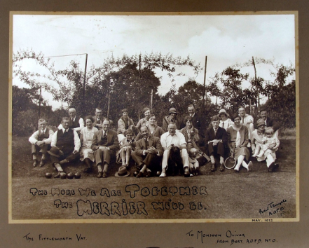 "Sepia photograph dating from around 1925 of the Ancient Order of Froth Blowers taken outside the Swan Inn in Fittleworth. Around 22 people are seated on a grassy bank. Written on the photograph with black ink is the phrase ""The More We Are Together the Merrier We'll Be""."