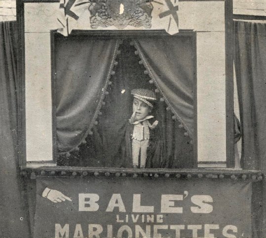 Someone performs as a puppet in a miniature theatre for a seaside show.