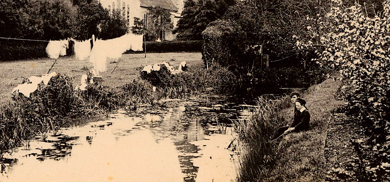Cropped sepia image of a river, with church in background. Two young boys sitting on bank, washing hung on line by river