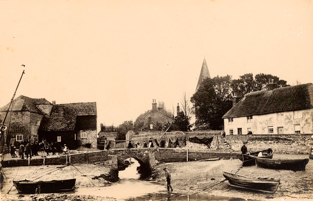 Sepia image of a brick bridge surrounded by buildings, boats and people. There is a church visible in background. There are also nets drying on stone walls