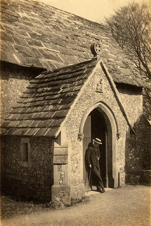 Sepia image of the south entrance to the church. A well-dressed man leans against the door.