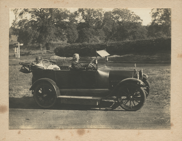 Side view of soft top car with the roof down, Carruthers at the wheel with Beatrice in the rear