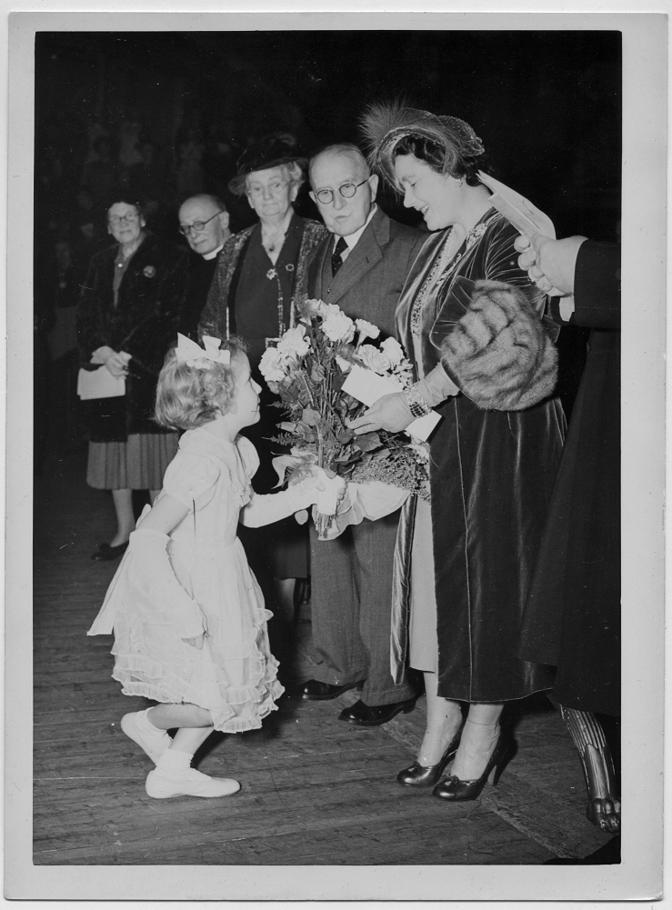 Corfield standing next to the Queen Mother who is being presented with a bouquet of flowers by a curtsying young girl