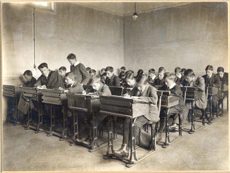 Rows of pupils sit at their desks in a schoolroom