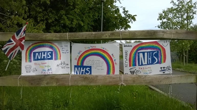 Three A4 sized posters wired between two wooden fence bars. A union jack flag is also tied to the top bar. The three posters have the NHS logo, plus rainbows as the centre point. Phrases like Stay Safe, Stay Home and Stay Fit are written around in colourful felt tip pens.
