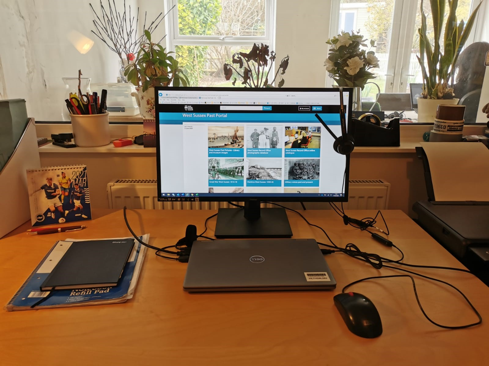 Photograph of a desk set up, with a monitor, laptop, mouse, notebooks and other office supplies.
