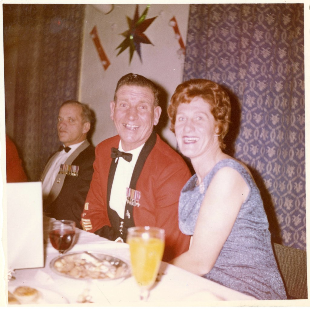 A couple seated at a formal dinner smiling for the camera. The man is wearing a red uniform with several medals across his chest.