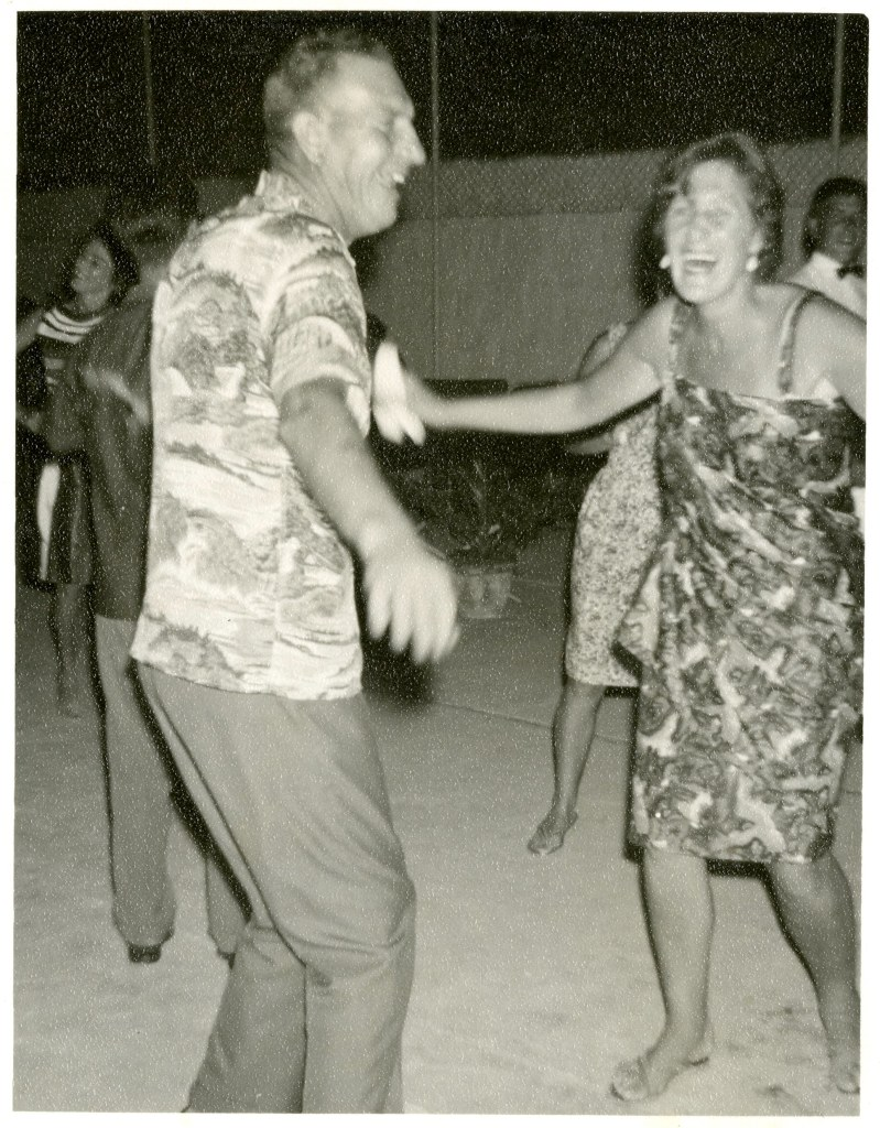 Black and white photgraph of a couple dancing. They are laughing, enjoying themselves. The man is wearing a print pattern shirt, and the woman is wearing a summer sun dress.