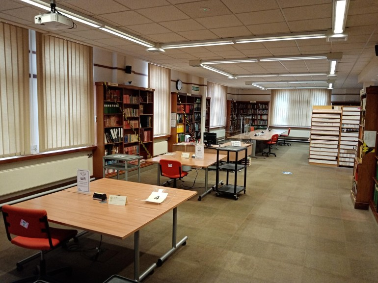Two tables spaced apart are in the foreground. Behind them are black and yellow taped off bookcases, the searchroom supervisor's desk, then a line of joined up table with three seats socially distanced apart.