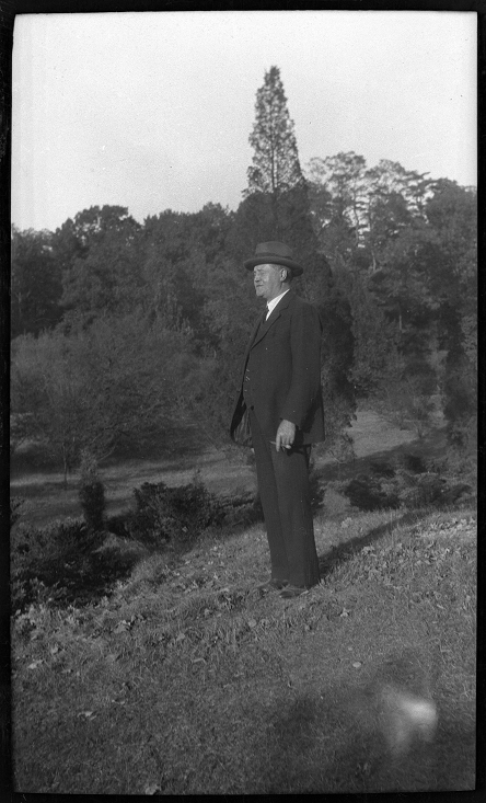 Black and white full body portrait of Wilson in a three piece suit and fedora hat.