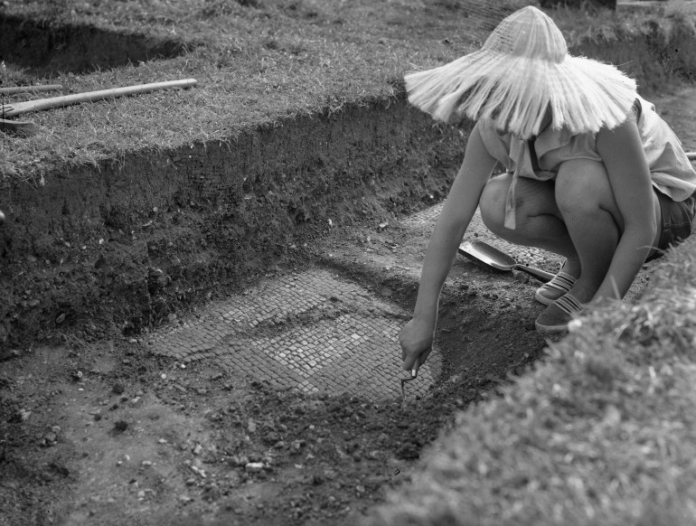 Archaeologist working at uncovering roman tiling underneath layers of dirt.