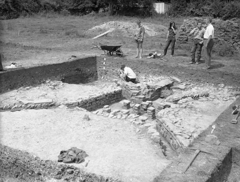 Five archaeologists working and talking at the dig.