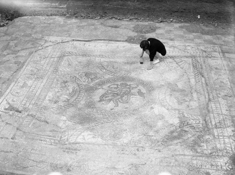 Archaeologist brushing clean the large Roman tiled floor.