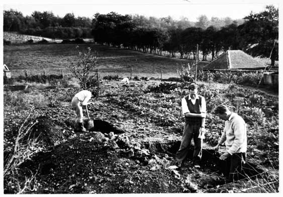Three people working in a trench on an archaeological dig in Pitlands Farm in Up Marden