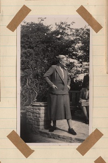 A photograph of Nancy Price taken from her scrapbook of work for the South Downs. Shows Nancy posing with her hands in her jacket pockets, standing in front of her wooden bench in High Salvington.