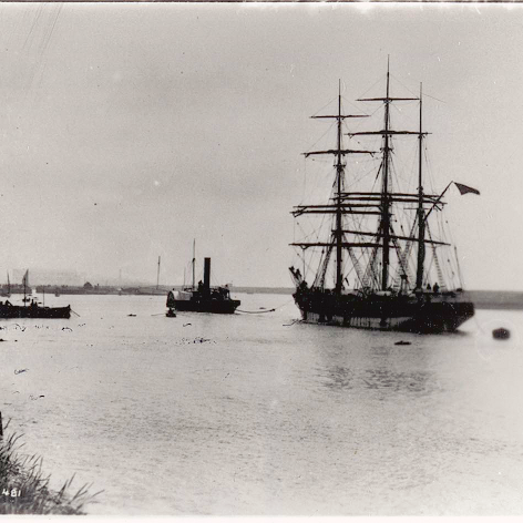 A large rig sailing ship is making its way along the harbour