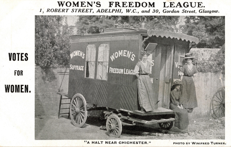 Two women are standing on rear step of the caravan with a third, seated woman (unidentified). Women's Suffrage and Women's Freedom League are written on the side of the caravan.