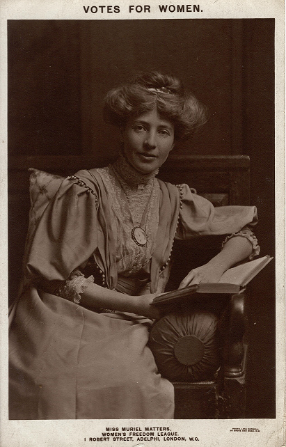 Sepia portrait of Muriel Matters, seated with a book, looking directly at the camera