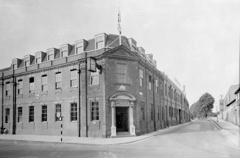 Black and white photograph of factory frontage / facade on East Street / East Walls, including the famous wishbone clock and front door.
