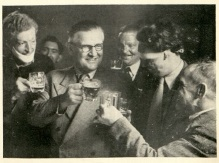 Five men with raised beer glasses standing around Doctor McIndoe, who also had a full glass of beer