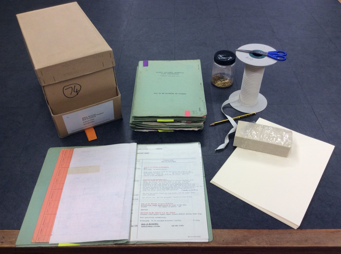 Image of the cataloguing of the collection in progress, with archival tape, scissors, a cleaning sponge, acide free card, brass paperclips and an archival box